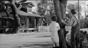 Jem, Scout and Dill stand and look upon the Radley house.